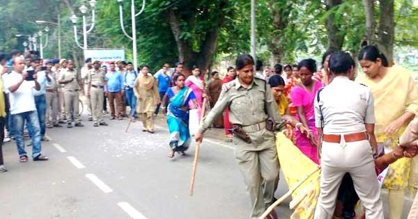 हड़ताल पर बैठी महिला को घसीट कर ले जाते पुलिसकर्मी
