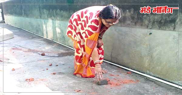 घर में फेंके गए ईंटों को चुनती पूर्व पार्षद की पत्नी