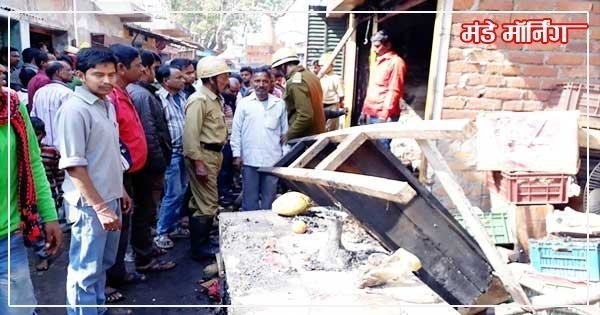 आग लगी दुकान को देखते दमकल कर्मी